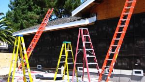 Viele bunte und verschiedene Leitertypen stehen vor bzw. lehnen an einem Haus.